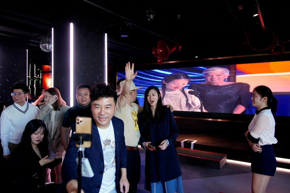 People get ready to pose for pictures with a video snippet of director Chloe Zhao's acceptance speech, as they attend a screening of the Academy Awards at a bar in Shanghai April 26, 2021. — Reuters pic